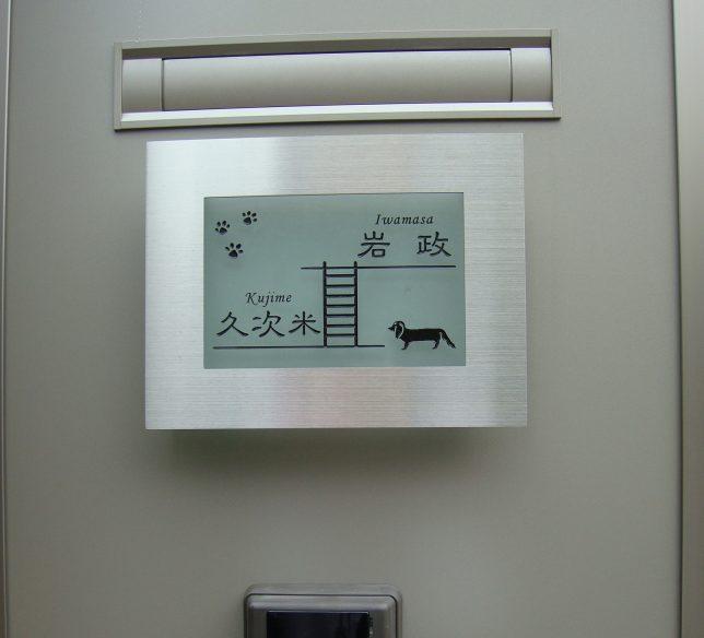 お客様の施工例「我が家の自慢の表札」より。二世帯のお名前と犬と足跡のデザインを入れられました。